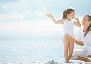 Mother dressing girl on beach