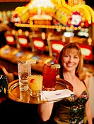 Waitress carrying drinks on tray, portrait (focus on drinks)
