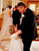 Flower girl (4-6) dancing with grandfather at wedding