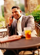 Businessman talking on mobile phone at outdoor cafe