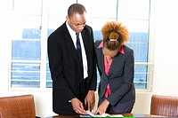 Businessman and a businesswoman reading a document in an office