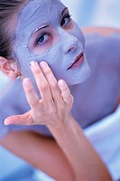 Woman applying purple facial