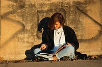 Girl Reading on Urban Street