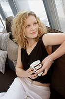 20 year old girl sitting on the sofa, with a coffee, smiling off camera