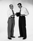 Two men standing, looking at clipboard