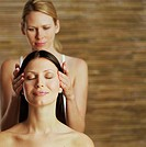 Two women, one with eyes closed receiving head massage from the other