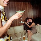 Woman holding cocktail in bar, focus on couple kissing on sofa
