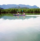 Young couple kayaking on lagoon, side view