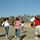 Group of children (9-11) running in playground, rear view