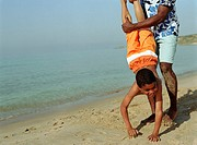 Man holding boy (7-9) upside down on beach