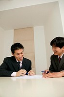 Two businessmen at table, holding pens, smiling