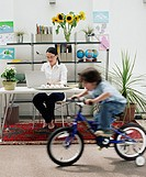 Woman using laptop at desk behind boy (3-5) riding bicycle