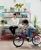 Woman using laptop at desk behind boy (3-5) riding bicycle