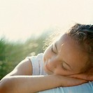 Girl (6-8) resting head on arms outdoors, eyes closed