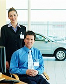 Two sales people in car showroom, smiling, portrait