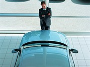 Salesman standing between pillar and car in showroom, elevated view