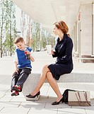 Mother and son (6-8) on stone bench outdoors, holding drinks