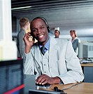 Businessman wearing telephone headset at desk, smiling, portrait