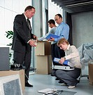 Four business people in office, woman sorting files for man