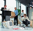 Four business people unpacking in office, woman using mobile phone