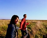 Couple running across field of tall grass (blurred motion)