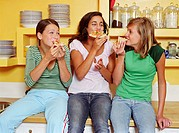 Three teenage girls (13-15) sitting on kitchen counter, eating pizza
