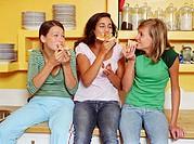 Three teenage girls (13-15) sitting on kitchen counter, eating pizza