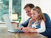 Father and daughter (3-5) at table using laptop computer, smiling