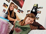 Two teenage girls in bedroom, smiling, portrait