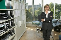 Businesswoman standing by desk, portrait