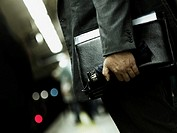 Businessman carrying briefcase and umbrella, mid section, side view