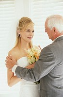Bride and father having conversation, smiling
