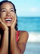 Woman on beach, touching face with hands, smiling