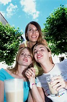 Three young women with drinks outdoors, smiling, close-up
