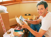 Man unpacking books from removal boxes, smiling, portrait