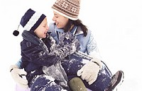 Mother and son (4-6) sitting in snow, laughing