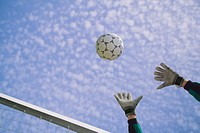 Male soccer goalie reaching for ball, low angle view