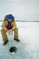 Mature man ice fishing on frozen lake