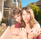 Teenage boy (14-16) hugging mother in driveway, portrait