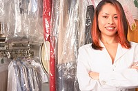Woman working behind counter at dry cleaners, portrait
