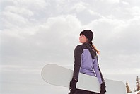 Teenage girl (16-18) holding snowboard, smiling, rear view