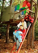 Three boys (10-12) sitting on treehouse ladder, portrait, autumn