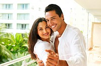 Couple on balcony in dancing position, smiling, portrait