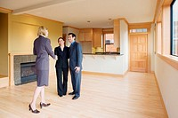 Man and woman in empty house, shaking hands with female realtor