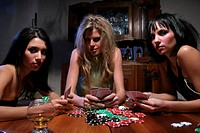 Three young women playing poker, portrait