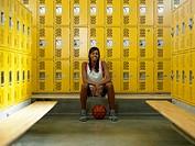 Teenage girl (15-17) basketball player in locker room, portrait