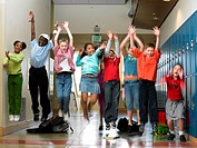 Children (8-10) jumping in school hallway (blurred motion)