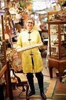Mature woman holding manuscript in an antique shop