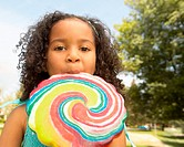 Girl (4-6) licking a giant lollipop in park, portrait