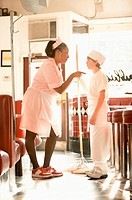 Waitress pointing at teenage boy (13-15) holding mop in diner